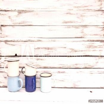 Enameled mugs in retro style on an old wooden background. ,