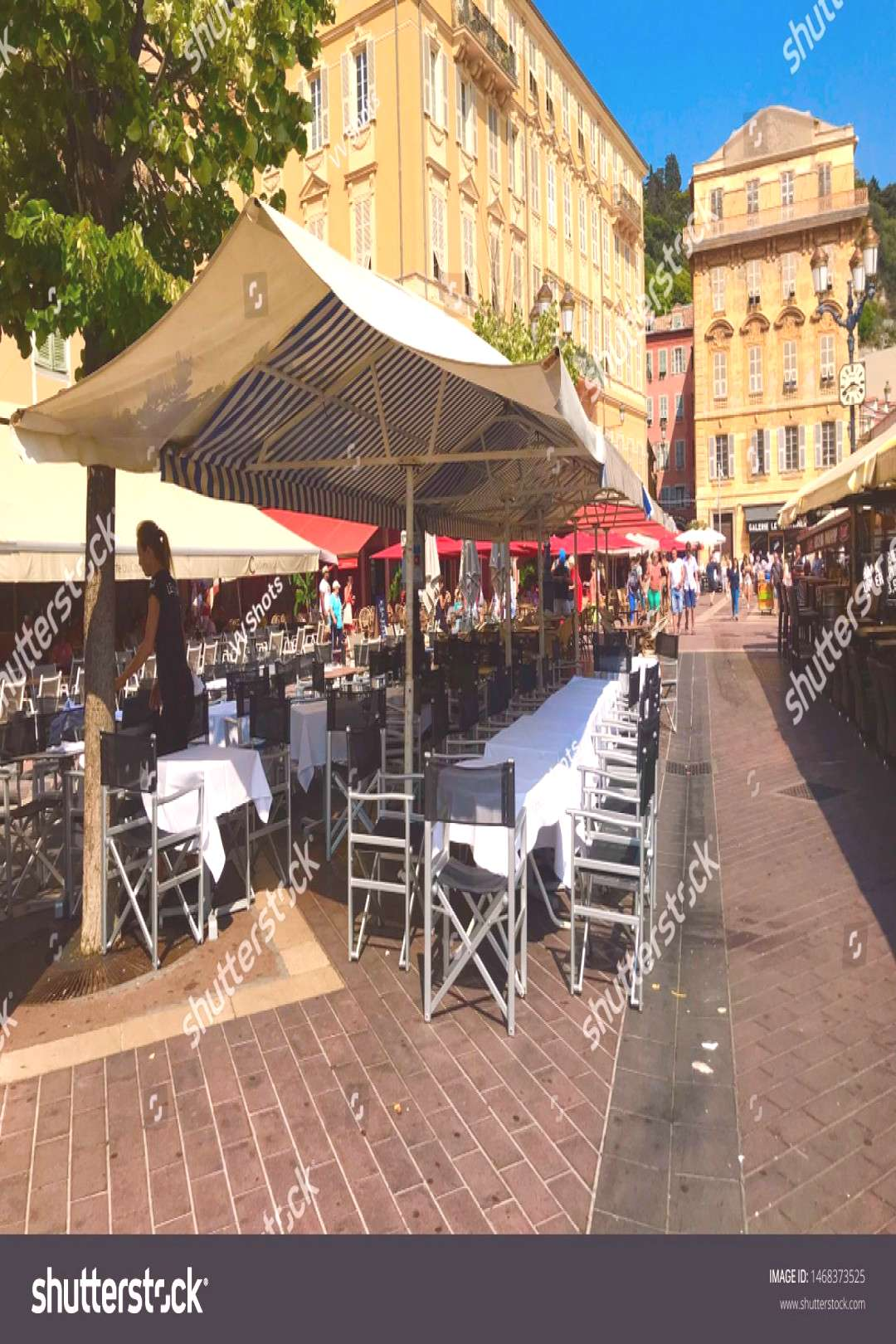 Nice, Nice \u002F France - July 21 2019: setting up dinner tables on Cours Saleya restaurants cafes