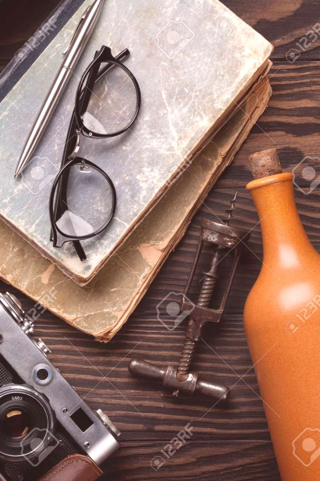 Retro table with vintage items. Camera, books, glasses, wine bottle. Top view Stock Photo ,
